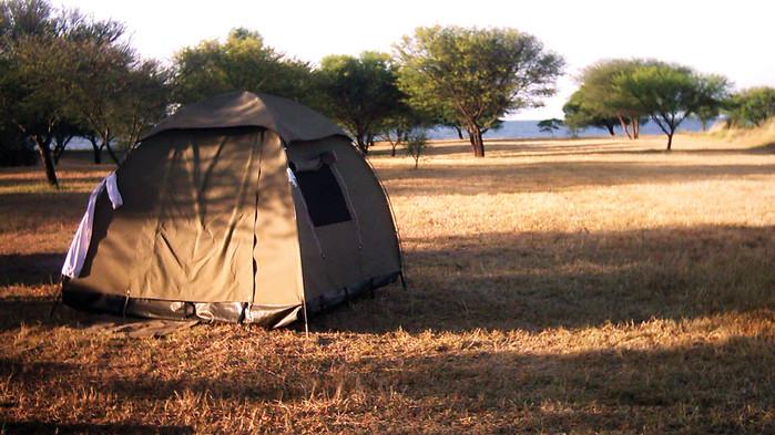 Man camper i enkle iglootelt langs vegen